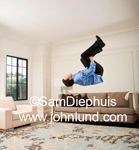 Photo of a man doing a back flip in his living room at home.